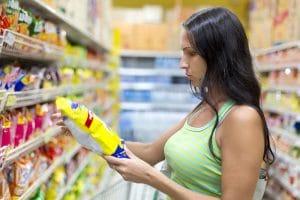 mujer mirando diferentes etiquetados de productos en el lineal de compra