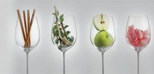 cuatro copas de vino llena de canela manzana y otras frutas en evocación de los olores del vino