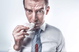 hombre comiendo un producto alimenticio con cara contrariada