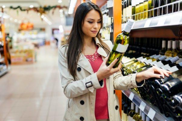 mujer en el lineal de venta de vino